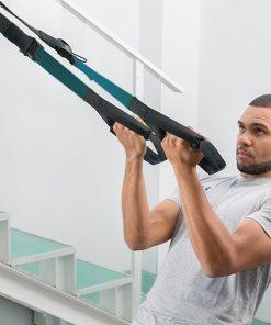 homme utilisant des sangles de suspension pour exercice biceps