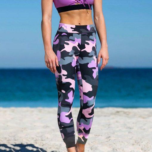 Legging treillis militaire sport porté par femme qui marche sur la plage