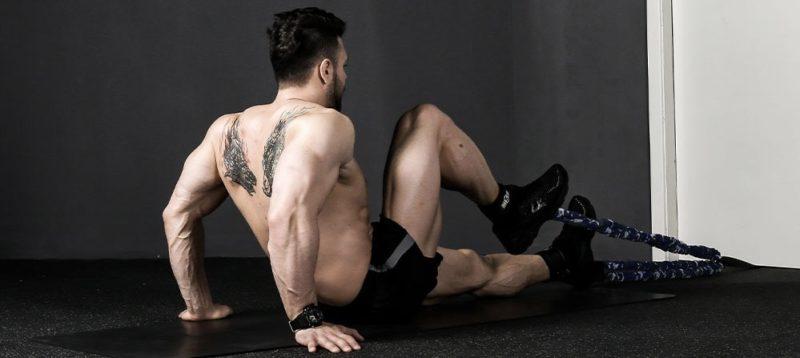 homme effectuant exercice de gainage avec elastiques de musculation