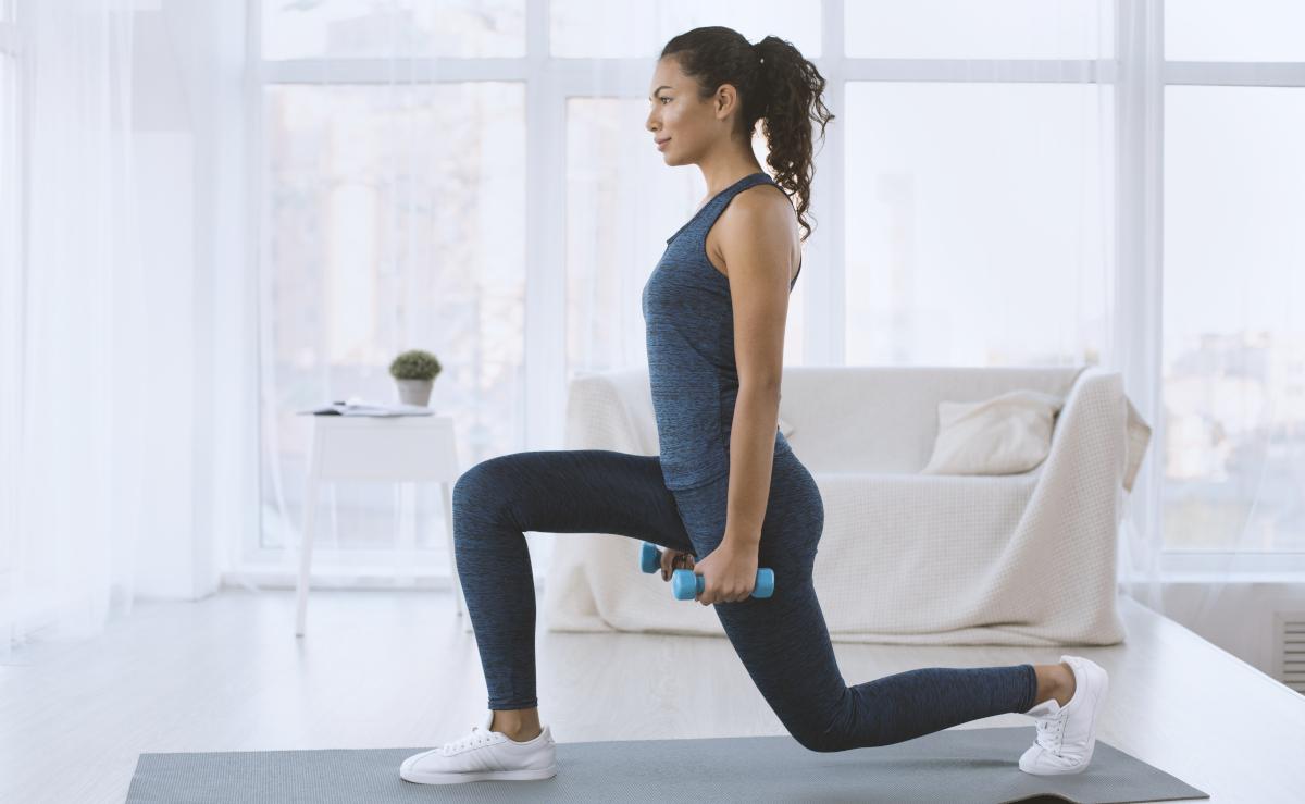 femme faisant exercice fente avant a la maison